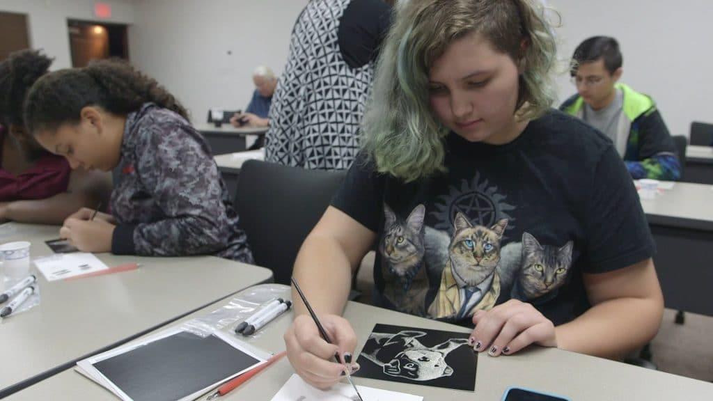 girl scratchboarding a dog in a scratchboard class provided by ScratchBoard University